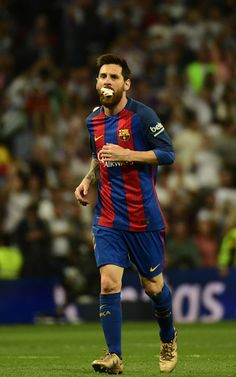 Barcelona's Argentinian forward Lionel Messi runs with a dressing on his mouth after being hit during the Spanish league football match Real Madrid CF vs FC Barcelona at the Santiago Bernabeu stadium in Madrid on April 23, 2017. / AFP PHOTO / PIERRE-PHILIPPE MARCOU