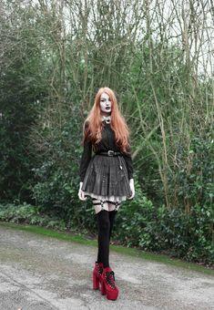 Olivia Emily wears Contrast Collar Black Blouse, Asos Western Belt, Pleated Faux Leather Skirt, Jakimac Leg Garter Harnesses, Unif Red Velvet Hellbound Boots