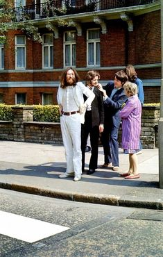 Paul preening Ringo with woman observing as Beetles prepare to walk across Abbey Road in the iconic pic.