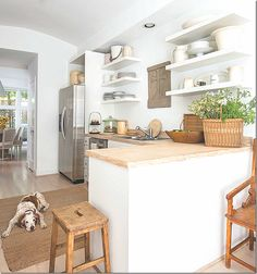 a great, airy look for a kichen. thick white floating shelves, white base cabinetry, pale wood countertops