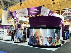 Veolia Transportation 50x50 Trade Show Exhibit Rental for APTA Expo 2011 - Ernest Morial Convention Center.    Large tapered tension fabric hanging structure 32' square by 5' high    Semi-private curved seating areas with tension double sided fabrics, cu