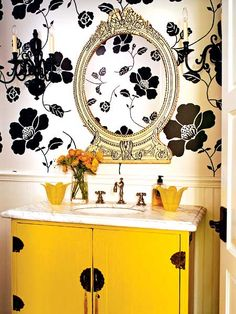 Canary yellow paint brightens up the sink console, and the large-scale, black-and-white floral wallpaper makes the tine space feel bigger. Finishing the room are inexpensive brass sconces painted matte black and a 1960s decoupage mirror. (Photo: Roger Davies)