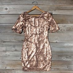 Piles of rose gold sequins sit atop a bronze base on this glittering dress. Expertly tailored, this dress features a short sleeve design, scoop neck and back detailing, and a soft stretch design to ensure the perfect fit. Bronze base with rose gold sequin detailing throughout. Hits approximately just above the knee to mid-thigh. The perfect glittering party dress.