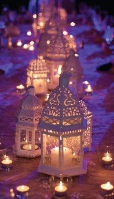 Moroccan lanterns cast a lovely glow here, this table really sparkles with all the lit votives. Love!