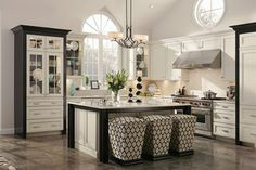 Like the furniture style china cabinetry! The bold pairing of white cabinet doors and drawer fronts with black crown molding creates striking visual interest in this luxurious kitchen.