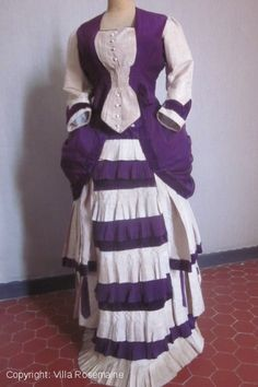 """1880 day dress or walking dress, inspired by the """"Polonaise"""" dress from the eighteenth century fashion, the running backs hoops with cotton ties are integrated into the """"queue d'écrevisse"""" in order to emphasize the hips and pleated front. The bodice, lined with striped cotton and boned, is composed as the skirt, with a deep purple woolen Chalis. Velvet ribbons and matching contrast of an ivory silk. Pearl buttons with eyelets and hooks at the folds of the waist."""