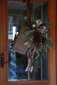 Baskets are ideal tools for door decor. We filled this one with holiday greens and finished off with a pretty ribbon.