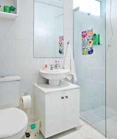 """Os dois banheiros do apê são iguais, mas foram personalizados. Adesivos de bichinhos enfeitam o destinado às crianças. """"Para os pais, toalhas, tapete e adornos podem dar um toque de cor"""", sugere a arquiteta Cecilia Belluci. Nesses cômodos diminutos, Cecilia decidiu usar um gabinete que abraça a pia de coluna. """"Dessa forma, o tampo do móvel serve para apoiar produtos de higiene e objetos que não cabem na borda do lavatório."""""""