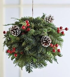 Add a sweet touch to your holiday decor with this beautiful evergreen kissing ball. The Christmas evergreen ball first originated in the Middle Ages, but came back into fashion during the Victorian era as a symbol of love and romance—much like mistletoe. Comprised of noble fir and western red cedar with accents of red berries and snow-dipped pinecones, this stunning arrangement will be a unique and festive addition to your home. Rustic Christmas Crafts, Outdoor Christmas Planters, Victorian Christmas Decorations, Yule Crafts, Christmas Greenery, Christmas Centerpieces, Christmas Love, Christmas Balls, Christmas Wreaths