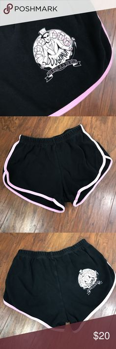"""American Apparel AA Voodoo Doughnuts 🍩 Shorts L Voodoo Doughnuts Shorts Black with pink trim Features signature Voodoo Doughnuts emblem  Size L American Apparel, high rise, elastic waist band shorts Bought from DT Portland VD new this summer Worn a few times but run small in my opinion Garment measures flat: Elastic Waist measures approximately 12"""" across Rise measures approximately 10"""" Inseam measures approximately 3"""" American Apparel Shorts"""