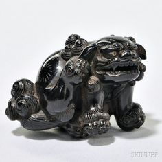 Ebony Netsuke Carving of a Lion, Japan, 19th century, seated on its right hind leg, its left leg raised to its ear, finely carved and incised details, inlaid eyes and pupils, signed on base, ht. 1 1/4, wd. 1 7/8 in.