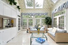 Solarium family room with skylights, french doors leading to the backyard, white floor and cabinets with striped blue and white furniture
