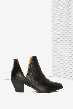 This ankle boot features a black glitter upper, slanted stacked heel, slits at sides, and slightly pointed toe.
