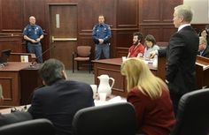 Accused Aurora theater gunman James Holmes (3rd from R) listens to Arapahoe County District Attorney George Brauchler (R) at his arraignment in Centennial, Colorado March 12, 2013. A Colorado judge presiding over the case of Holmes entered a not guilty plea on his behalf on Tuesday to charges that he went on a shooting spree nearly eight months ago that killed 12 moviegoers. REUTERS-R.J. Sangosti-Pool