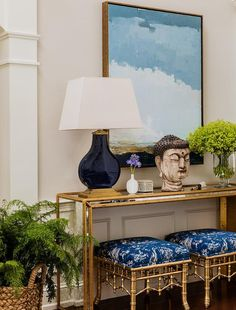 Chinoiserie foyer boasts a pair of gold bamboo stools accented with blue seat cushions tucked under a gold trim mirrored waterfall console table topped with a navy lamp, Cloris Table Lamp, and Buddha head statue under art.