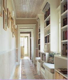 Hallway library with window seats below windows that bathe the space in natural light. What a lovely way to use an otherwise wasted space -- I love this!