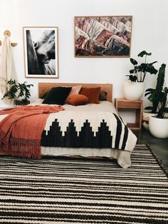 Bohemian style bedroom with orange accents and striped black and white rug