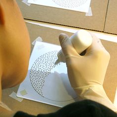 Eunice constructs the collagraph plate by putting down the modeling paste marks. Collagraphs