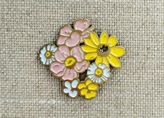 A bouquet of native mid-western wildflowers, never wilts! Elegant and whimsical. Features rudbeckia, prairie roses, wild violas, and fleabane.  1 Soft Enamel Lapel Pin. Butterfly Clutch. Antique Brass Finish.
