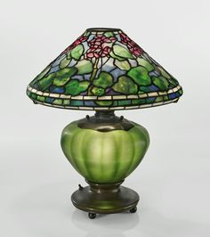 "Tiffany Studios ""GERANIUM"" TABLE LAMP with an illuminated blown-glass base shade with small early tag impressed TIFFANY STUDIOS leaded glass, favrile glass, patinated bronze 20 in. (50.9 cm) high 17 in. (43.2 cm) diameter of shade circa 1900."