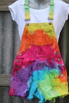 242555e40ea Colorful overall shorts in a rainbow tie dye color theme and a white  tshirt. Distressed jean gives it a bit of flair.