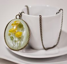 Resin Pendant real dried buttercup necklace by FaintOfArt on Etsy, $25.00 (Artist: Kristi Dunlap)