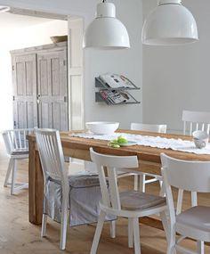 De witte eetkamer wordt zacht door de ronde vormen die terugkeren in de lampen, schaal en stoelen.