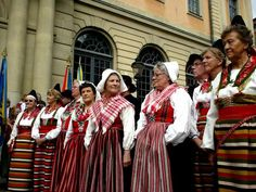photo of Sweden, Stockholm, Stortorget Gamla Stan, celebration of people from Hälsingland in traditional Swedish dress (folkdräkt), traditional women in red and white striped clothes ready to dance