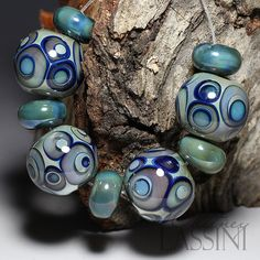 This unique set of round beads look like they came straight from the deep ocean! Multiple layers of iridescent blue/green silver glass dots give