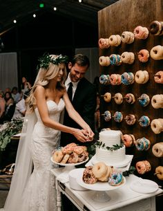 Elegant white wedding cake + a donut wall.. yes please! | Image by Luke and Mallory