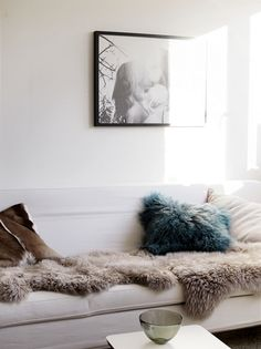 white walls, white sofa, skin rug, throw pillows