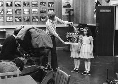 Behind-the-scenes photo on the set of The Shining. Lisa and Louise Burns, who portrayed the Grady Twins, prepare for a shot on the Games Room set. Kelvin Pike operates the camera and Camera Assistant Peter Robinson holds the slate.