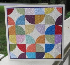handmade quilt card ... square format ... quarter circles in squares ... pretty hodge podge of color ... embossing folder texture ... fun look!