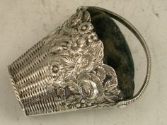 George III Novelty Silver Basket of Flowers Pin Cushion A rare George III novelty silver Pin Cushion made in the form of a wicker basket full of flowers, with swing handle. By Samuel Pemberton, Birmingham, c1800