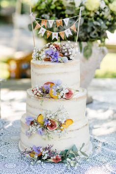 Hochzeitstorte im Vintage Look mit echten Blumen und Wimbelkette als Cake Topper.  Foto: Verena Hohmann Fotografie