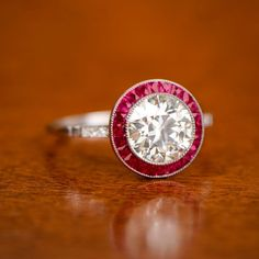 A beautifully crafted ruby halo and diamond ring centering a warm 1.75ct old European cut, K color, VS1 clarity diamond. Surrounding the diamond is a row of gem quality rubies. Along the shoulder is one bezel set diamond. This ring is entirely hand-crafted in platinum in the