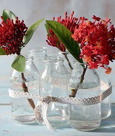 As garrafinhas simples viraram um belo arranjo de mesa unidas por uma fita de renda. Flores miúdas são perfeitas para o arranjo. Produção de Luana Prade