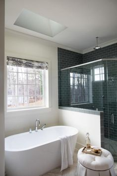 A large window and well-placed skylight over the soaking tub allow lots of natural light inside the open and airy master bath.