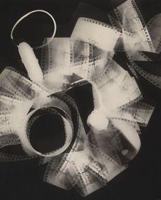 Rayograph (Raiografia) 1923.  Raiografia era o termo que Man Ray usava para definir seu próprio estilo de fotografia sem uso de câmera. Ele colocava os objetos diretamente sobre o papel fotográfico e expunha à luz. Aqui, ele usou uma faixa de filme de 35-mm.