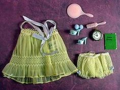 Barbie Sweet Dreams #973(1959-1962)    PINK or YELLOW    Baby Doll PJ Top & Panties  Blue Hair Ribbon with Metal Ring  Light Blue Open Toe Heels with Blue Pompons  Brass Clock  Diary  Wax Apple    Features textured sheer tricot baby doll pajamas with embroidery on the bodice. The blue ribbon straps tie in a bow at back. The matching panties have a tiny bow trim on either side. Frequently the elastic in the panties will be stretche