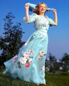 color photo of Marilyn Monroe in light blue dress with flowers and scarf
