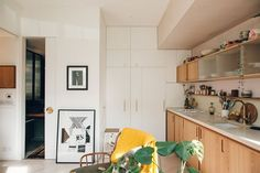The refrigerator is built in to this kitchen wall. How a Tiny London Loft Fits a Lot of Living Into 500 Square Feet — Apartment Needs, Apartment Therapy, Apartment Kitchen, Hidden Cabinet, London Apartment, Kitchen Cabinetry, Cupboards, Kitchen Reno, Cuisines Design