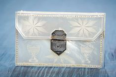 French Mother-of-Pearl Needle Case,Possibly Palais Royal. The folio-shaped case has delicate incised decorations including flower-filled urn on its exterior,with little silver clasp,and opens to silk-lined interior needle case with two packages of tiny German needles. French,early 1800's. http://Theriaults.com/