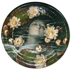 Meissen charger of Ophelia  Germany  circa 1899  Large Meissen porcelain charger hand painted on green ground with portrait of Ophelia drowned in a brook,with waterlilies; interpretion of the original by pre-Raphaelite painter, John Everett Millais. Signed to front and to underside, by Ludwig Sturm; blue crossed swords to underside.