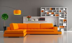 Modern living room design with bright orange sectional sofa, grey walls, orange lamp and large white bookshelves