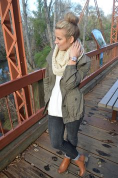 Army green jacket, chunky scarf, and boots.