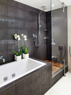 Contemporary black tile bathroom with a teak floor in shower area.