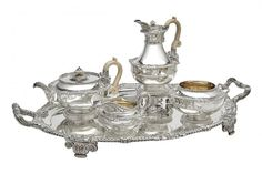 George III Sterling Silver Tea and Coffee Service Paul Storr, London, 1813 Comprising a teapot, coffee pot on stand, cream jug, sugar bowl and two-handled tray, each of circular form, the shoulders with a gadrooned and foliate shell border, with serpent-form handles, engraved with heraldic arms, on a spreading fluted foot. Height of coffee pot on stand