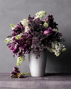 Pair a tall vase with a riot of lilacs -- as many as you can fit! -- for a display with drama and movement. Parrot tulips in purple with white edges add texture and pick up both colors of lilacs. To assemble this arrangement, we used a narrow-necked vase; we added white lilacs, followed by the tulips, and then purple lilacs until the bouquet felt full and lavish.