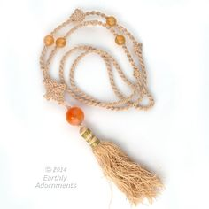 A Vintage Chinese export necklace from the 1970s. A beautifully knotted macrame necklace with knotted twists and Chinese eternal knots enclosing. Carnelian agate beads and ending with a silk basket tassel. Length of the necklace is 35 inches and tassel is 3 1/2 inches.